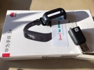 Der Clip, mit dem man den Fitness-Tracker am Schuh befestigen kann und das Ladegerät liegen auf der Schachtel, in der der Fitness-Tracker geliefert wurde.