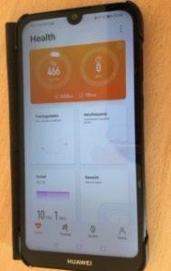 Smartphone mit geöffneter App. Man sieht die Startseite der App: Schrittanzeige, Schlaf, Gewicht.