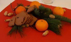 Mandarinen, Tannenzweige und Nüsse liegen auf einer Serviette zur Dekoration auf einem kleinen Tisch