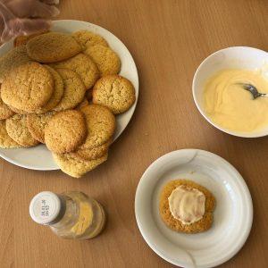 Ein Teller mit den fertig gebackenen Plätzchen. Auf einem kleinen Teller liegt ein Plätzchen, verziert mit Eierlikörguss. Ein Schälchen mit dem Eierlikörguss und eine Flasche mit einem Rest Eierlikör stehen daneben.