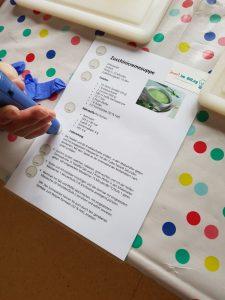 Fr. E. hält den AnyBook Audiostift auf den Sticker, der den 1. Zubereitungsschritt für die Zucchinisuppe vorliest.