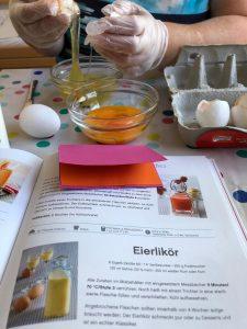 Fr. E. trennt das Eigelb vom Eiweiß. Im Vordergrund sieht man das aufgeschlagene Kochbuch mit dem Eierlikörrezept.