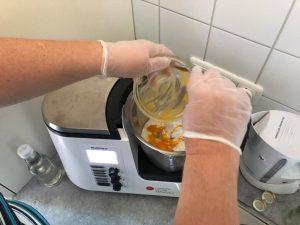 Fr. E. gibt die Zutaten in den Mixbehälter der Küchenmaschine