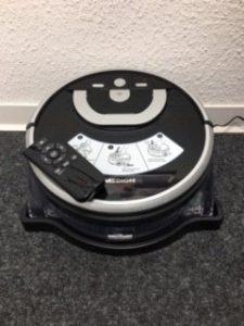 Wischroboter Medion MD 18379 steht auf dem Boden an der Wand. Auf dem Gerät liegt die dazu gehörende Fernbedienung